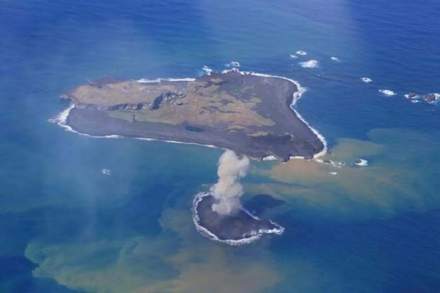 写真1。西之島と新島の噴火活動の遠景。11 月24 日昼前。 ストロンボリ式噴火を繰り返す新島。西之島と新島を南東側上空から撮影。