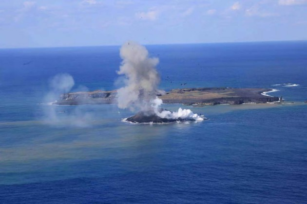 写真1。西之島と新島の噴火活動の遠景。11 月24 日昼前。 海に達した溶岩流の先端からは水蒸気の白煙が上がる。同じく南東側から撮 影。