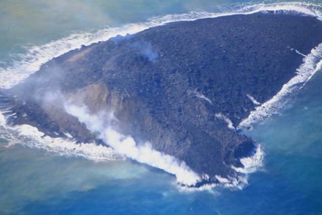 写真2。新島の全景と溶岩流。2013 年11 月24 日昼前。 黒色の溶岩流が中腹から流れ手前の海に流入。右(北)側に古い流れでできたと思われる土手が発達。左手前(南東)と左奥(南西)に斜 面崩壊でできた褐色の崖が発達している。青白い噴煙が頂部火口から上がっている。東から撮影。