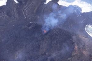 写真 4. 主火口付近の様子.マグマが見えている主火口(黄色矢印)のほかに,東側斜面に小火口が認められる(白矢印).写真奥は12月初旬までに東側に流出した溶岩.火砕丘はその上に裾野を広げている.西側から撮影.