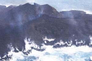 写真 6. 火砕丘西側から流出している溶岩流.溶岩先端部では,高温の溶岩と海水との接触により蒸発した海水が激しく立ち昇っている.西から撮影.