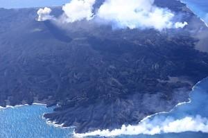 写真1:東側から見た西之島。左上にある中央火砕丘ではストロンボリ式噴火を繰り返しており,その裾野から樹枝状の溶岩流が四方に広がる。東側では溶岩が海に注いでいる。