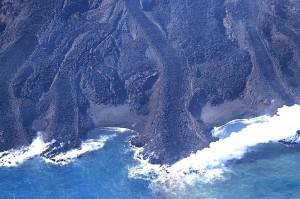写真2:東側で海に注ぐ溶岩流。溶岩堤防に囲まれた新鮮でごつごつした表面の溶岩が海中に没し,水蒸気を上げている。
