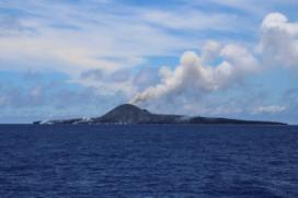 写真1 南東側から撮影した西之島(6月15日12:22).東側山腹には小丘が成長し,南東端では溶岩流が海に流出して水蒸気の白煙を上げている.